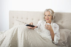 Ältere Frau, die beim Trinken des Kaffees im Bett fernsieht Lizenzfreie Stockbilder