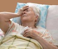 Ältere Frau, die am Bett liegt Lizenzfreies Stockbild