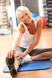 Ältere Frau, die Übungen in der Gymnastik ausdehnend tut Stockbild