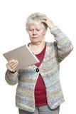 Ältere Frau, die den Tablettecomputer schaut verwirrt verwendet Lizenzfreies Stockbild