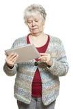 Ältere Frau, die den Tablettencomputer schaut verwirrt verwendet Lizenzfreie Stockbilder