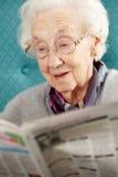 Ältere Frau, die in der Stuhl-Lesezeitung sich entspannt Stockfoto