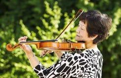 Ältere Frau, die draußen Musik durchführt Stockfoto