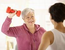 Ältere Frau, die Dumbbellübung tut Stockbild