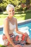Ältere Frau, die durch Garten Poolin sich entspannt Lizenzfreie Stockfotografie