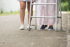 Ältere Frau, die einen Wanderer mit Pflegekraft verwendet Lizenzfreie Stockfotos
