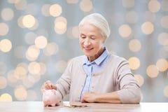 Ältere Frau, die Geld zum Sparschwein steckt Lizenzfreies Stockfoto
