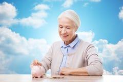 Ältere Frau, die Geld zum Sparschwein steckt Stockfoto