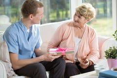 Ältere Frau, die Geschenk gibt Lizenzfreie Stockbilder