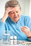 Ältere Frau, die ihr Medizin einnimmt Stockfotos