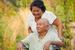 Ältere Frau, die ihren behinderten Ehemann drückt Stockfoto