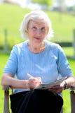 Ältere Frau, die im Garten sich entspannt Lizenzfreie Stockfotos