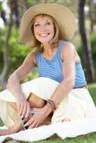Ältere Frau, die im Sommer-Garten sich entspannt Lizenzfreies Stockbild
