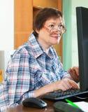 ?ltere Frau, die mit Computer arbeitet Stockfoto