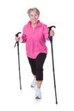 Ältere Frau, die mit Wanderstöcken geht Stockfotografie