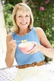 Ältere Frau, die Schüssel Frühstückskost aus Getreide genießt Lizenzfreie Stockbilder