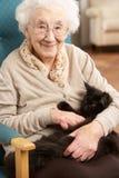 Ältere Frau, die sich zu Hause im Stuhl entspannt Stockbilder
