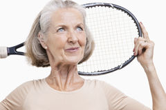 Ältere Frau, die Tennisschläger über ihrer Schulter gegen weißen Hintergrund hält Stockfotografie