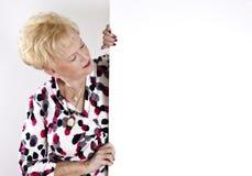 Ältere Frau, die unbelegtes weißes Zeichen anhält Lizenzfreie Stockfotos