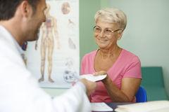 Ältere Frau, die Verordnung empfängt Stockbild