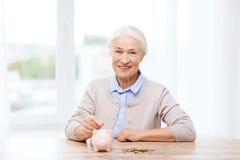 Ältere Frau, die zu Hause Geld zum Sparschwein steckt Lizenzfreie Stockfotografie