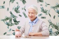 Ältere Frau, die zu Hause Geld zum Sparschwein steckt Stockfotografie