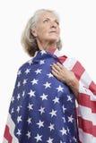 Ältere Frau eingewickelt in der amerikanischen Flagge gegen weißen Hintergrund Lizenzfreie Stockbilder