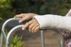 Ältere Frau gebrochenes Handgelenk unter Verwendung des Wanderers Lizenzfreies Stockfoto