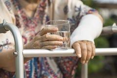 Ältere Frau gebrochenes Handgelenk unter Verwendung des Wanderers Stockfotografie