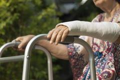 Ältere Frau gebrochenes Handgelenk unter Verwendung des Wanderers Lizenzfreie Stockfotos