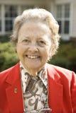 Ältere Frau im roten Mantel draußen lächelnd Stockbild