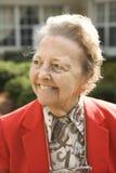 Ältere Frau im roten Mantel draußen lächelnd Stockfoto