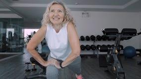 ?ltere Frau macht squattings in der Turnhalle Ältere Frau der älteren Frau macht Übungen eines Sports in der Turnhalle stockbild