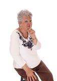 Ältere Frau mit dem Finger über Mund Lizenzfreie Stockfotografie