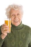 Ältere Frau mit einem Saftglas Stockbild