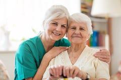 ?ltere Frau mit ihrer weiblichen Pflegekraft lizenzfreie stockfotos