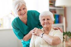 ?ltere Frau mit ihrer weiblichen Pflegekraft lizenzfreie stockfotografie