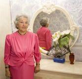 Ältere Frau nahe Spiegel Stockbilder
