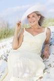 Ältere Frau in Sunkleid u. -hut am Strand Stockfoto