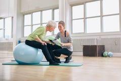 Ältere Frau und der Trainer, die Gesundheit betrachtet, berichten Stockfotos