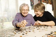 Ältere Frau und jüngere Frau, die Puzzlespiel tut Lizenzfreie Stockfotografie