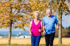 Ältere Frau und Mann, die Eignungsübungen tuend läuft Stockfotografie