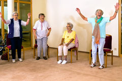 Ältere Frauen, die für Übung stehen und sitzen Stockbild
