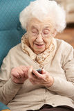 Ältere Frauen-wählende Zahl auf Handy Stockbild