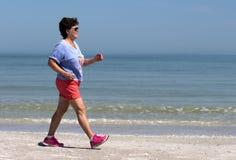 Ältere Frauenenergie, die auf einen Strand geht Stockfoto