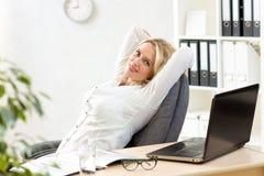 Ältere Geschäftsfrau, die bei der Arbeit im Büro sich entspannt Lizenzfreie Stockfotografie