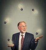 Ältere Geschäftsmannexekutive im jonglierenden Spielen der Klage mit Glühlampen Stockbild