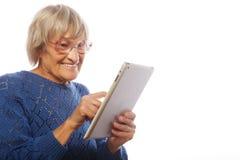 Ältere glückliche Frau, die ipad verwendet Stockfotos