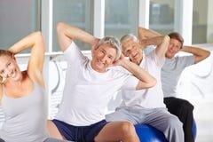 Ältere Gruppe, die hinteres Training auf Turnhallenbällen tut Lizenzfreie Stockbilder