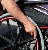 Ältere Hand auf Rad des Rollstuhls Lizenzfreies Stockfoto